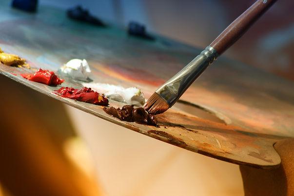 pensel och färgklickar i akryl mot färgpalett i trä