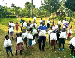 Ggita and the kids hold up generation donations of food.