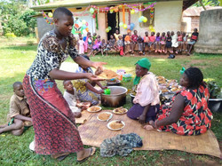 Locals help with feeding the children during Christmas celebration.