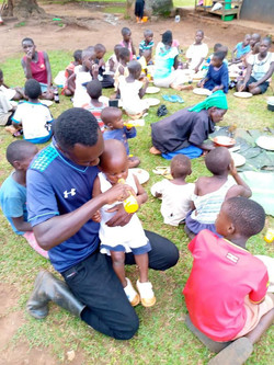Ggita helps one of the orphanage's littlest ones take a drink.