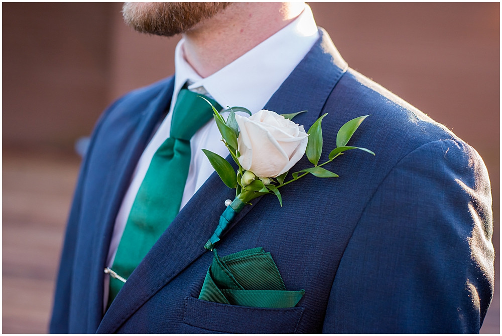 navy suit with green napkin square and boutonnière