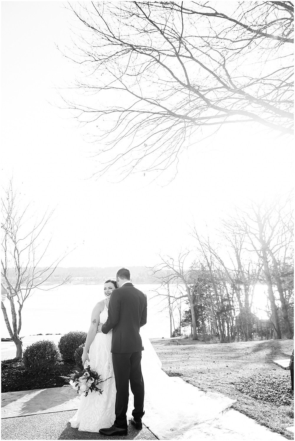 black and white of the bride and groom whispering secrets