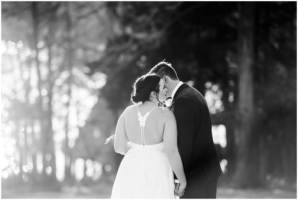 black and white of groom whispering in bride's ear, back of dress