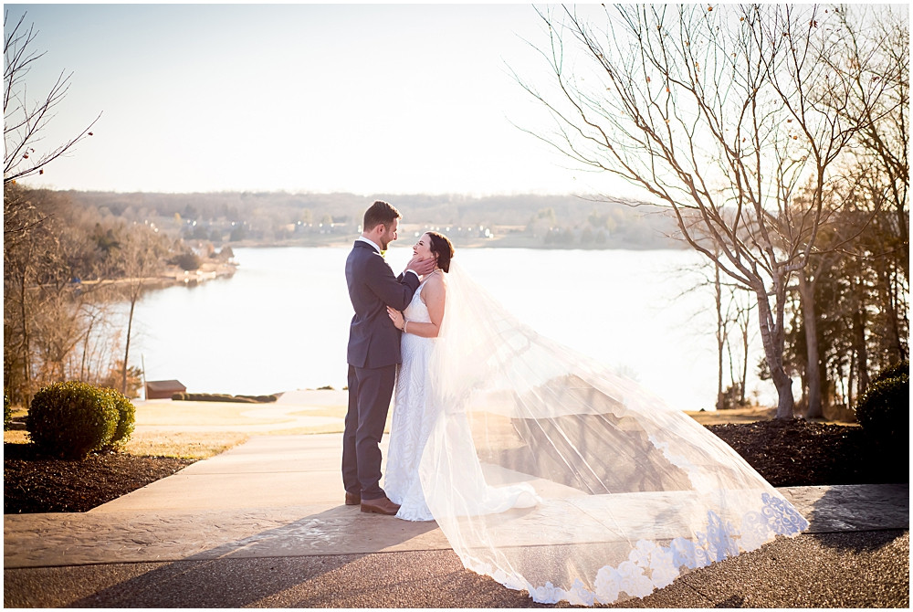 Sophia and Ryan smiling and looking at each other with the water behind and veil in the wind.