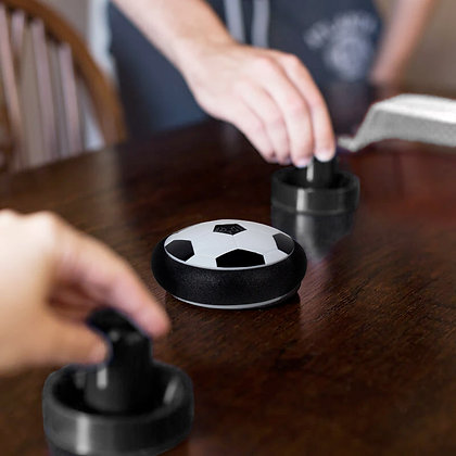 Playing Tabletop Air Football at home on polished table