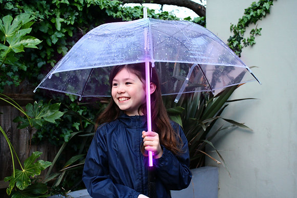 Young girl holding Brolli childrens LED Umbrella with pink illumination