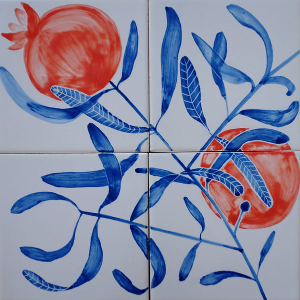Handpainted artistic tiles of pomegranates in blue and red with curling, wild leaves by Maxime Longden. Using traditional techniques in Lisbon, Portugal, contemporary designed and painted tiles by commission.