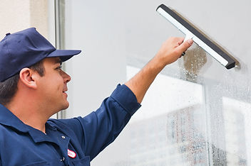 man cleaning window of office building