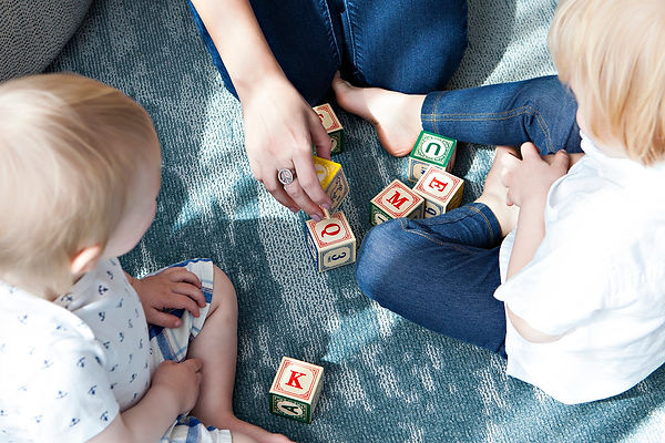 Kids and educator playing with wooden block