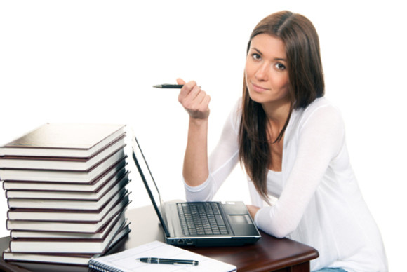 Brunette Business woman sitting in an office working on her laptop computer pc with a pen in the hand offer to sign contract, on the table books, paper and notebook isolated on a white background