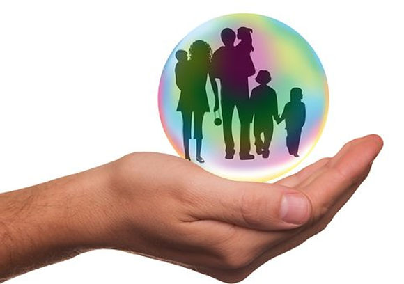 Hand holding global family in a bubble.
