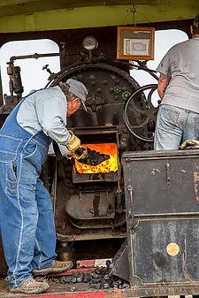 Stoking the firebox | Beth Hostetler Photography