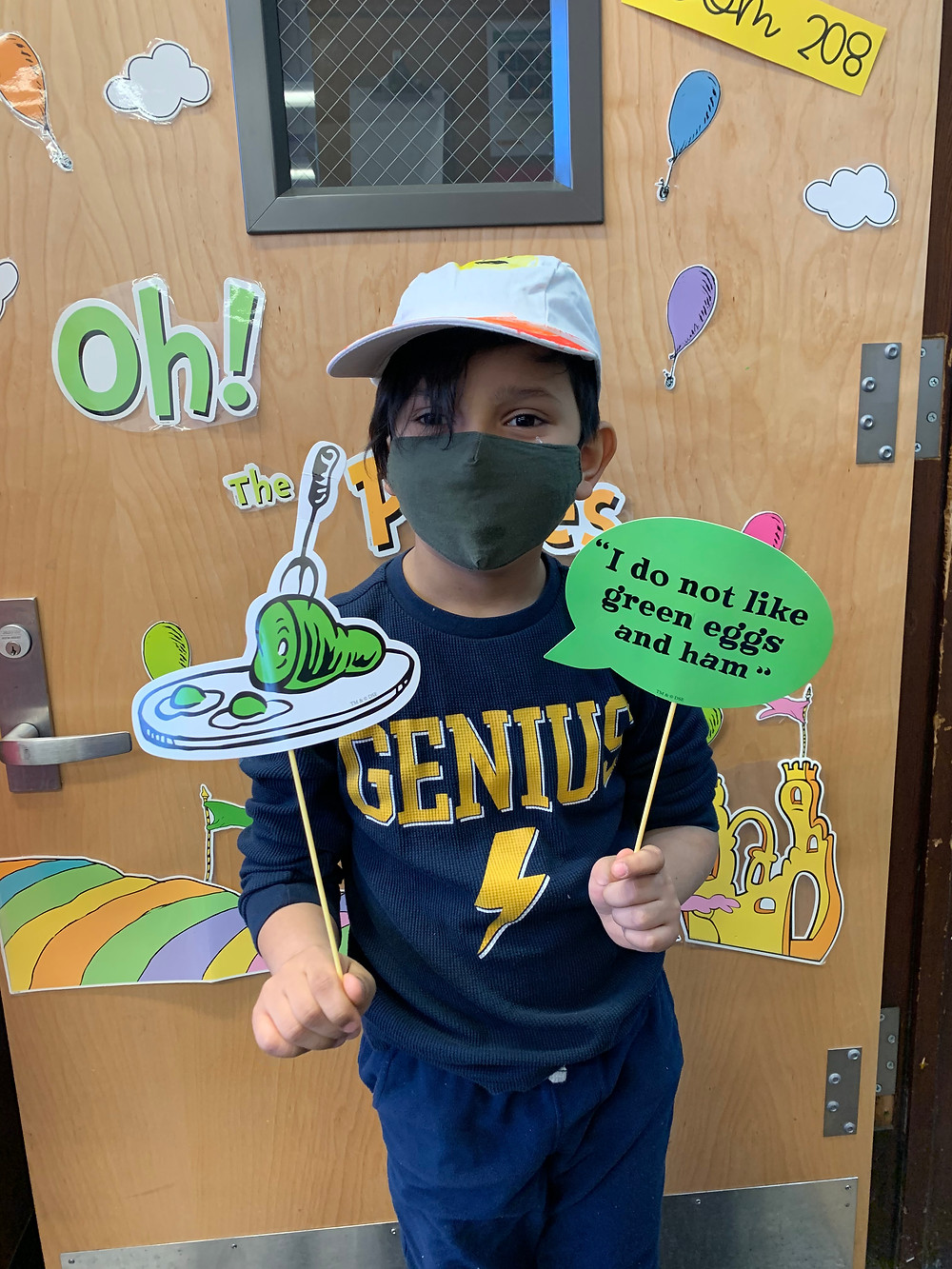 A 2nd grader holds up Green Eggs and Ham signs to celebrate Dr. Seuss!
