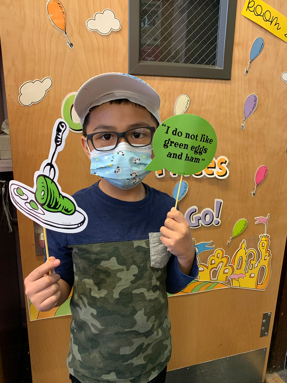 2nd grader holding up Green Eggs and Ham signs