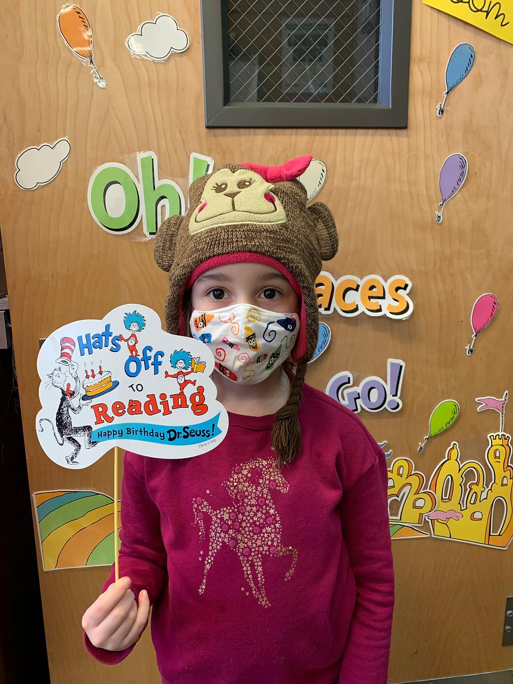2nd grader in monkey hat holding Dr. Seuss sign