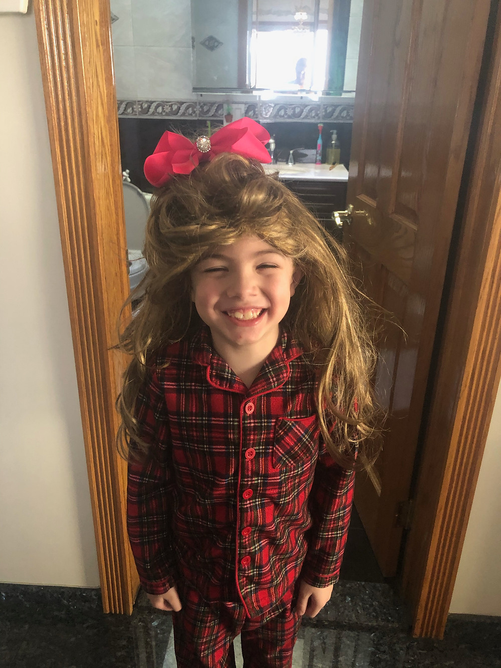 1st grader celebrates Wacky Hair Day in a long wig.