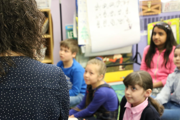 A class sits listening to the teacher