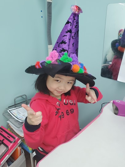 Student in a purple witch's hat for Crazy Hat Day!