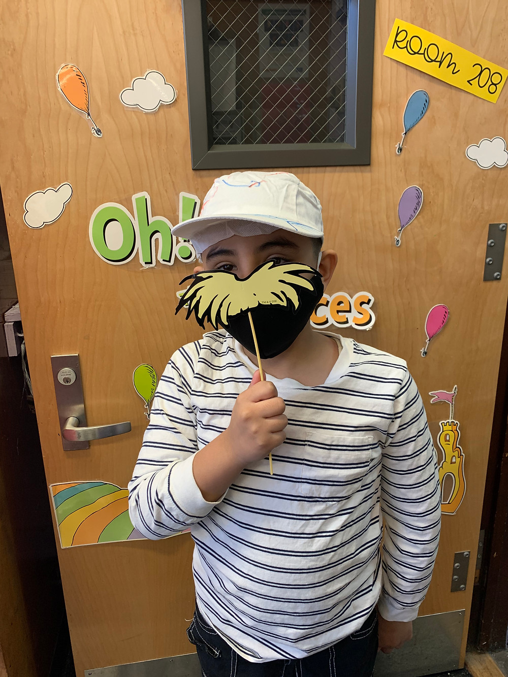 2nd grader celebrating Dr. Seuss with a Lorax mustache