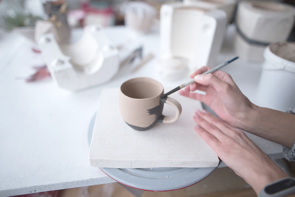 Female hand painting a ceramic mug