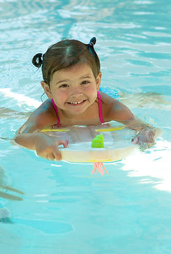 Child in pool on floating device learing how to swim
