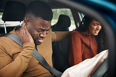 African American man holding neck from car accident