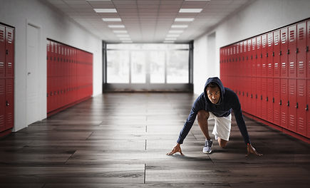 A student althlete doing stretches in a school hallway