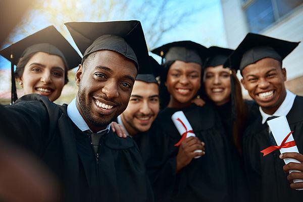 A group photo of graduates holding diplomas