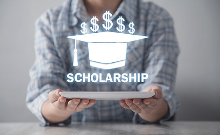 A man holding a graphic image of a draduation cap and the words Scholarship