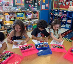 Kindergarten children drawing at desks