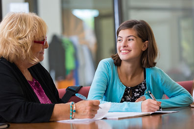 An advisor talking to a young student about college preparation