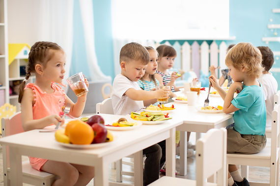 Group of children eating healthy food in