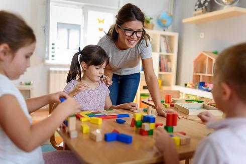 Preschool teacher with children playing