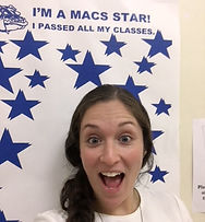 Female staff poses in front of a poster titled I'm a MACS star