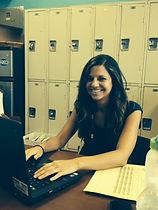 Smiling Female teacher types on a laptop