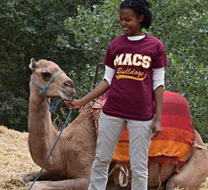 Payroll secretary stands with her macs shirt on in front of a camel