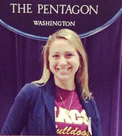 Female teacher takes picture in front of the pentagon sign