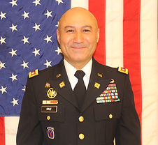 Colonel Cruz stands in uniform in front the American flag
