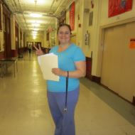 Smiling female teacher stands in school hallway