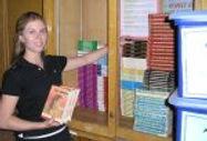 Female teacher stacks books in a bookcase