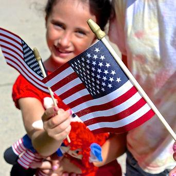 Young girl waving American flag. Photo by Joe Pregadio.