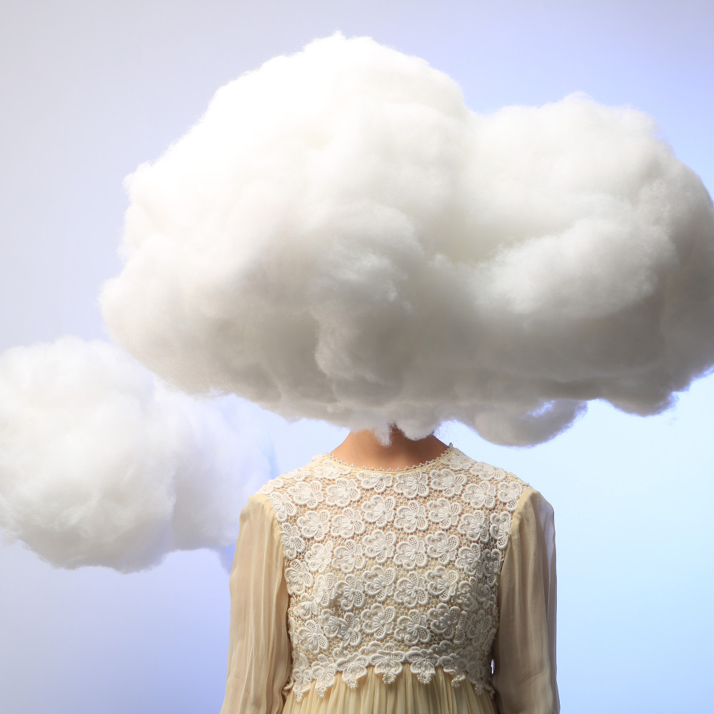 Picture of a women with clouds for her head, to illustrate the foggy brain symptom some women experience during menopause
