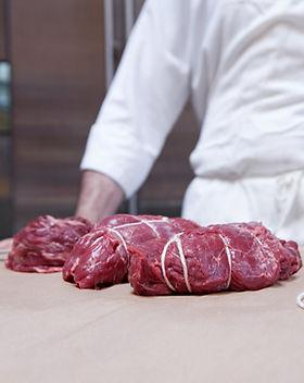 Carnicero con la carne de vaca