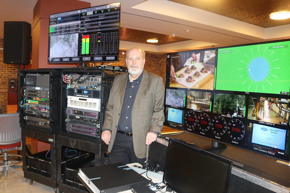 Wes Simpson standing beside a multiviewer and two racks of equipment that comprise the ST 2110 demonstration provided by Diversified shown at the SMPTE New York meeting on June 6, 2019.