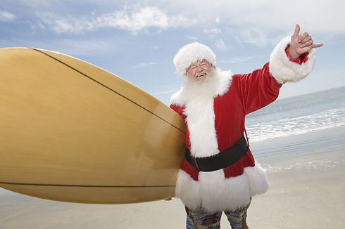Happy Santa Claus with surf board on bea