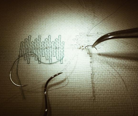 Vernähung eines Leinwandrisses mit chirurgischen Fäden