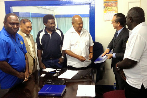 Pres Momis Bougainville and William Lawton in Papua New Guinea holding a national economic development program booklet