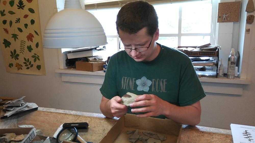 Figure 7: Stonerose employee, Andy Burkett, identifying a piece of alder leaf fossil.