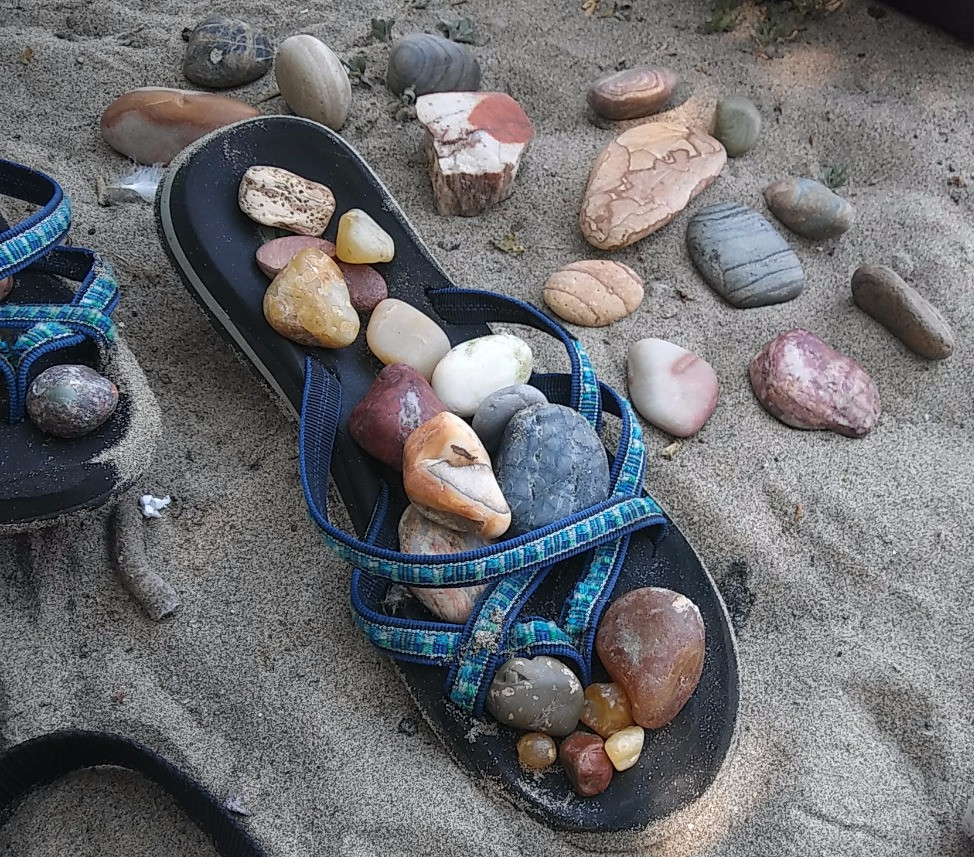 Figure 4: A sandy sandal stacked with agate, jasper, chert, and other rocks hounded during PIT tag recovery on the Columbia River.