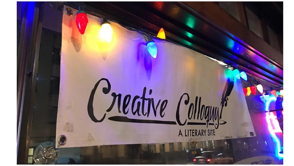 Figure 2: The banner for Creative Colloquy's monthly event, backlit in the glory of the shop formerly known as Black Kettle Bites & Brew. Photo credit: Creative Colloquy Facebook homepage.